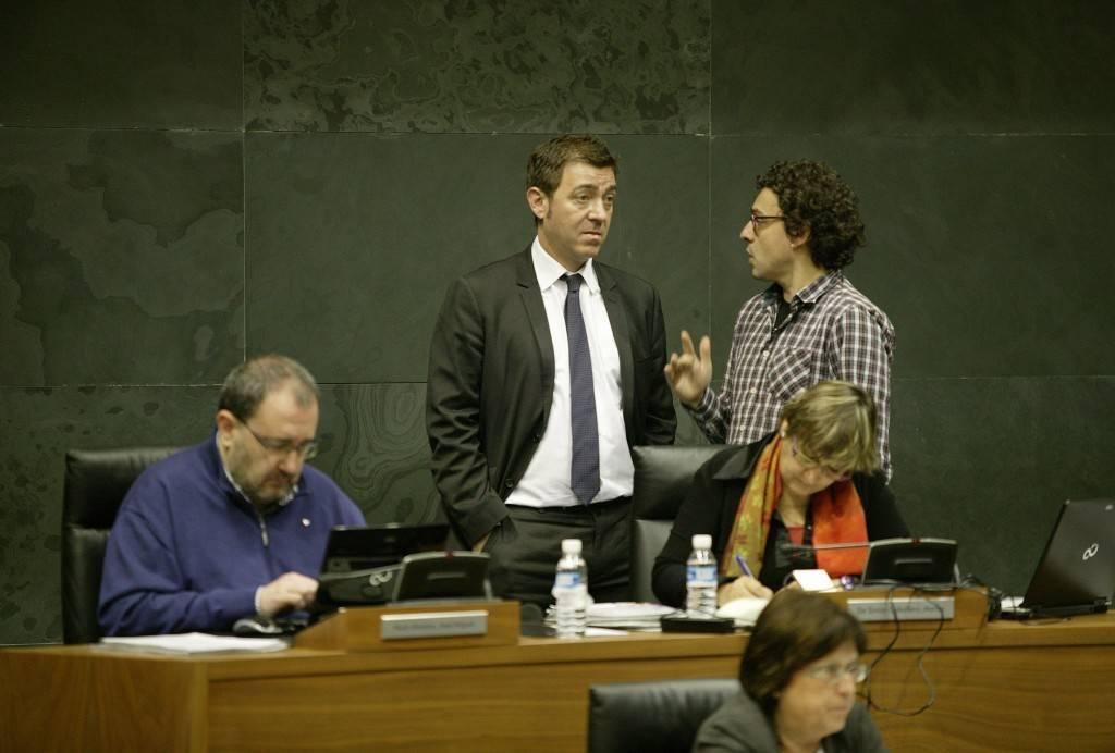 El portavoz parlamentario socialista, Roberto Jiménez conversa en un receso del pleno con Txema Mauleón, de Izquierda-Ezkerra. Sentados José Miguel Nuin, y Marisa de Simón, de I-E
